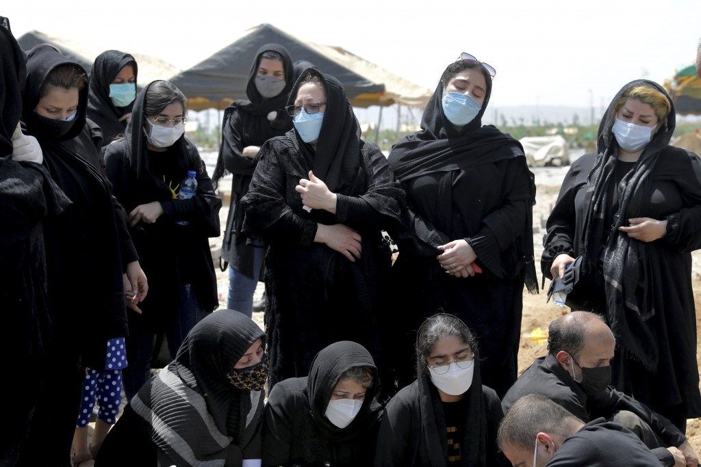 Mourners attend the funeral of a person who died from COVID-19, at the Behesht-e-Zahra cemetery just outside Tehran, Iran, Wednesday, April 21, 2021. ...