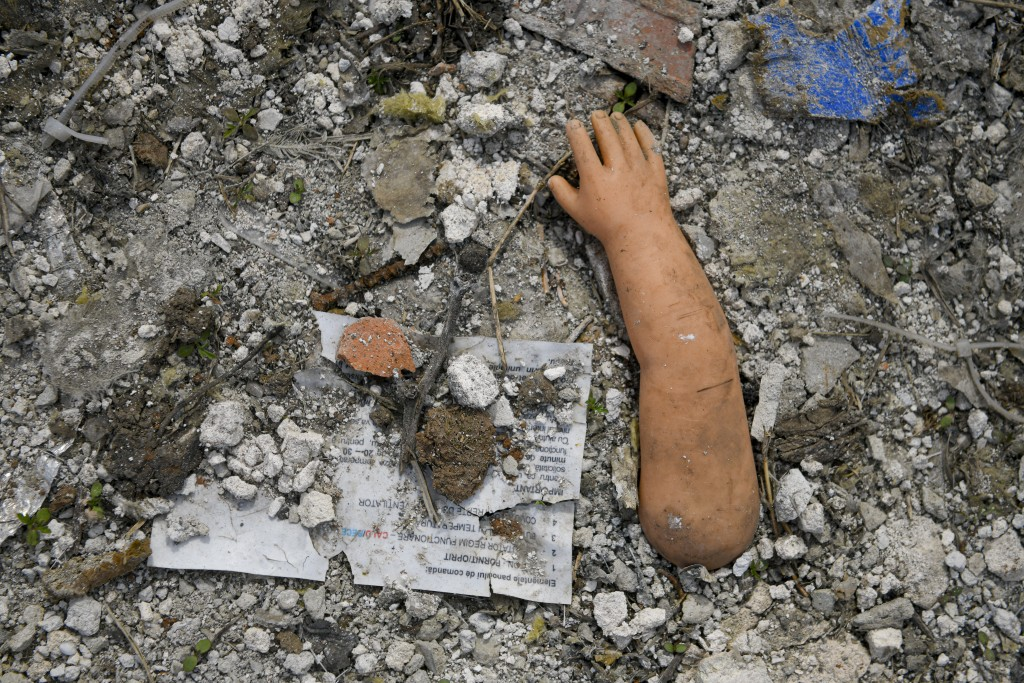 The hand of a doll litters the ground during a raid by the National Environmental Guard in Vidra, Romania, Tuesday, April 13, 2021. Many people in the...