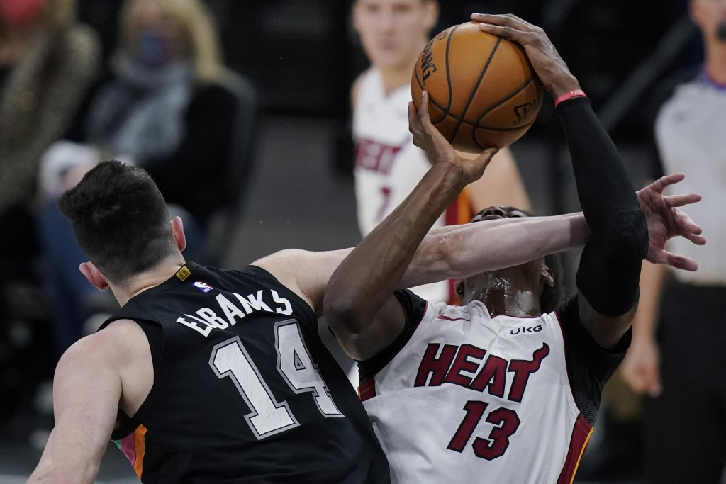 Miami Heat center Bam Adebayo (13) is fouled by San Antonio Spurs forward Drew Eubanks (14) as he drives to the basket during the second half of an NB...