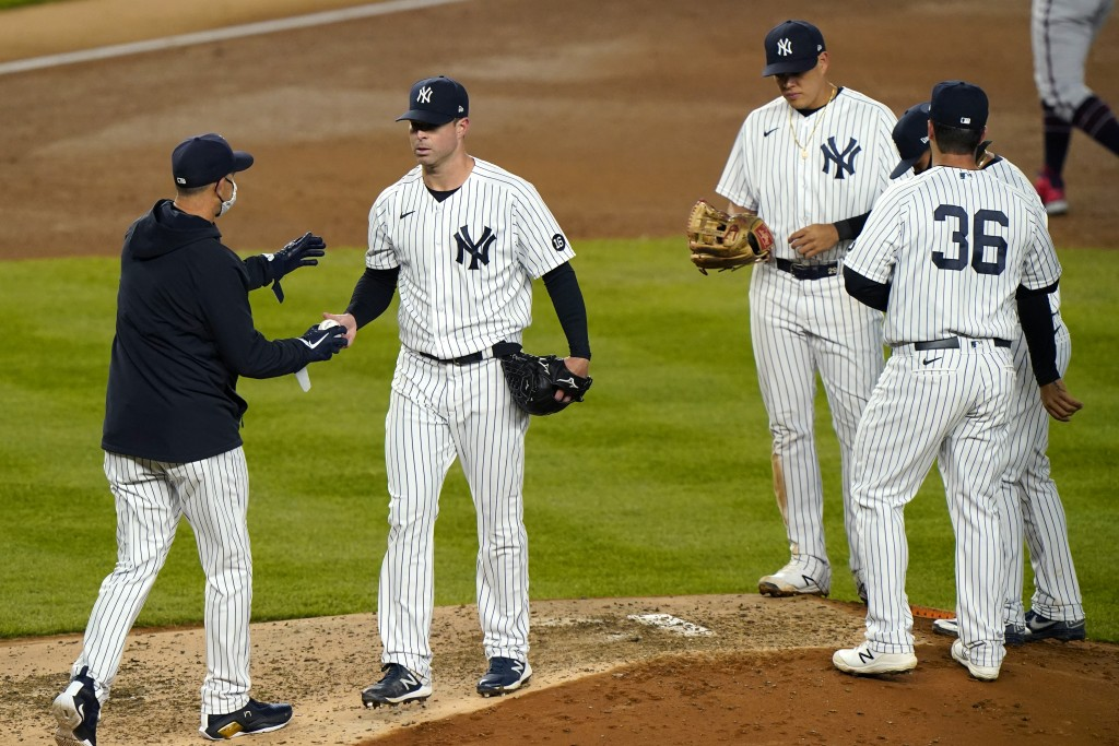 New York Yankees manager Aaron Boone. left, takes the ball from starting pitcher Corey Kluber as infielders stand on the mound during the fifth inning...