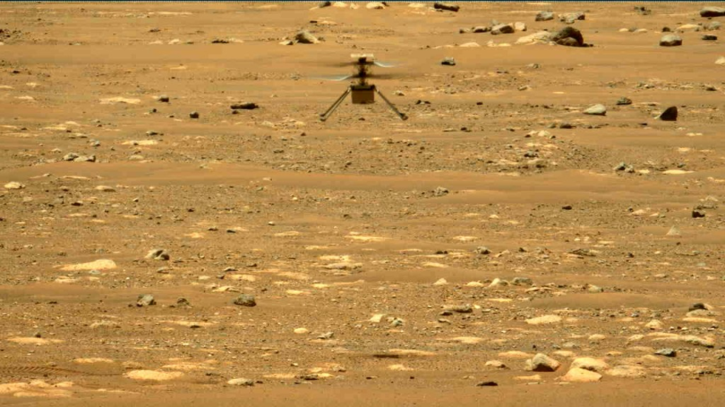 In this image made available by NASA, the Mars Ingenuity helicopter hovers above the surface of the planet during its second flight on Thursday, April...