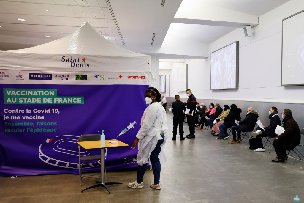 FILE - In this April 6, 2021, file photo, people wait to be vaccinated against COVID-19 at a vaccination center set up at the Stade de France stadium ...