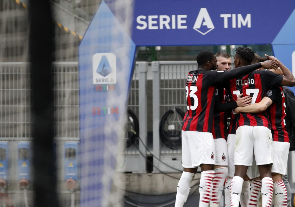 AC Milan's Hakan Calhanoglu celebrates with teammates after scoring his side's opening goal during the Serie A soccer match between AC Milan and Sassu...