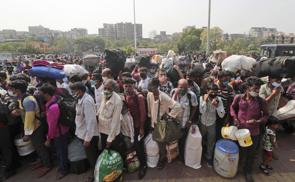 People wearing masks as a precaution against the coronavirus stand in queues to board trains at Lokmanya Tilak Terminus in Mumbai, India, Wednesday, A...