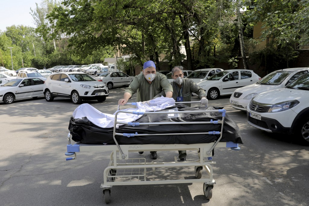 Hospital workers move two bodies of patients who died from COVID-19, at the yard of the Shohadaye Tajrish Hospital in Tehran, Iran, Sunday, April 18, ...