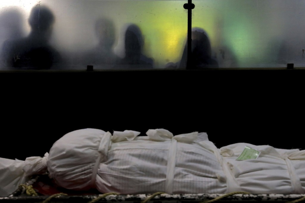 The body of a man who died from COVID-19 is prepared for a burial, at the Behesht-e-Zahra cemetery just outside Tehran, Iran, Wednesday, April 21, 202...