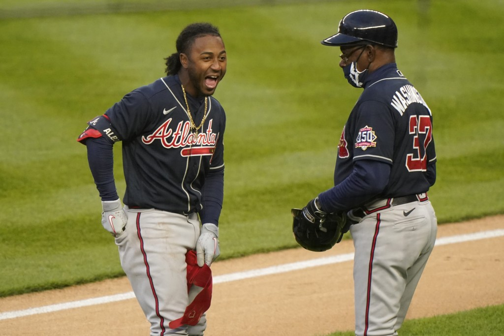 Atlanta Braves second baseman Ozzie Albies (1) laughs as he talks to third base coach Ron Washington (37) between innings of the team's baseball game ...
