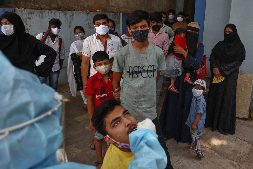 A health worker takes a mouth swab sample of a man to test for COVID-19 as others wait their turn to get tested at a hospital in Hyderabad, India, Mon...