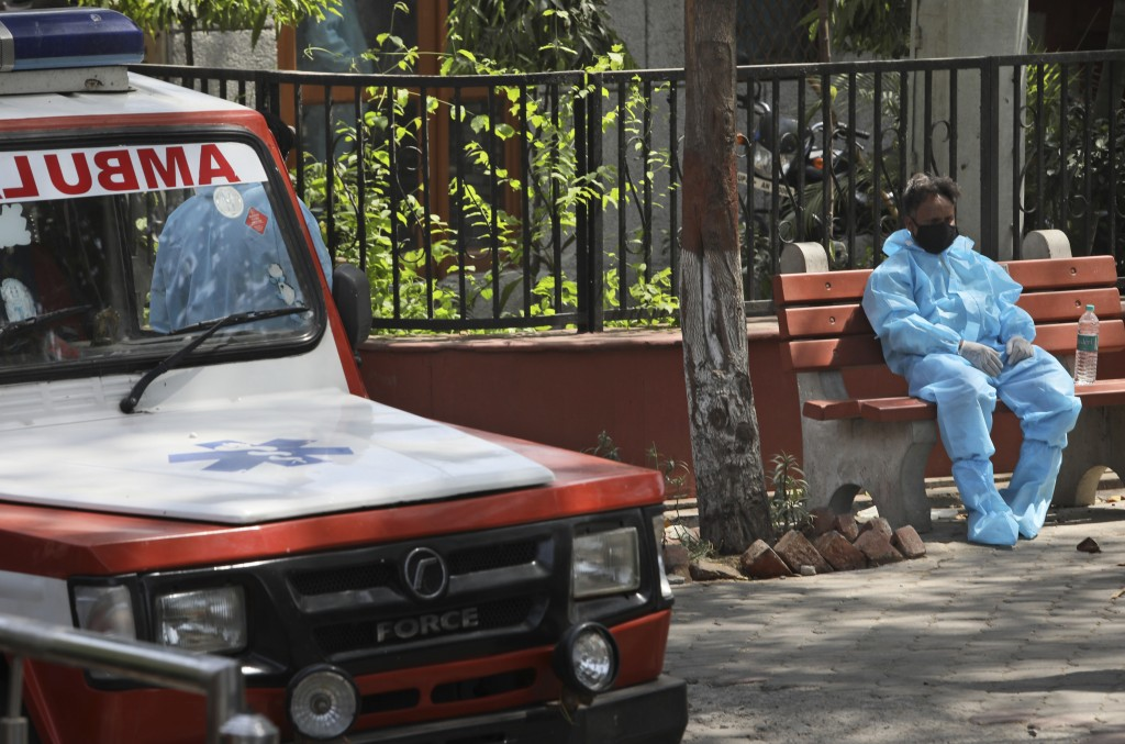 A Health worker sits on a bench after helping cremating victims of coronavirus, in New Delhi, India, Monday, April 19, 2021. New infections are rising...