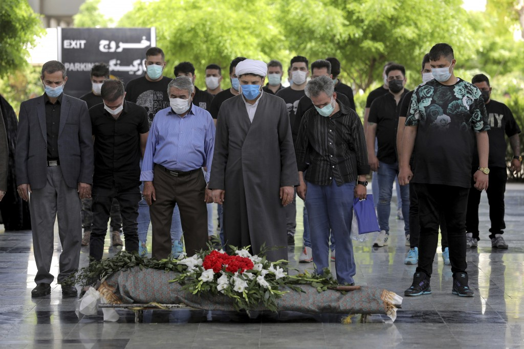 Mourners pray over the body of a person who died from COVID-19, at the Behesht-e-Zahra cemetery just outside Tehran, Iran, Wednesday, April 21, 2021. ...