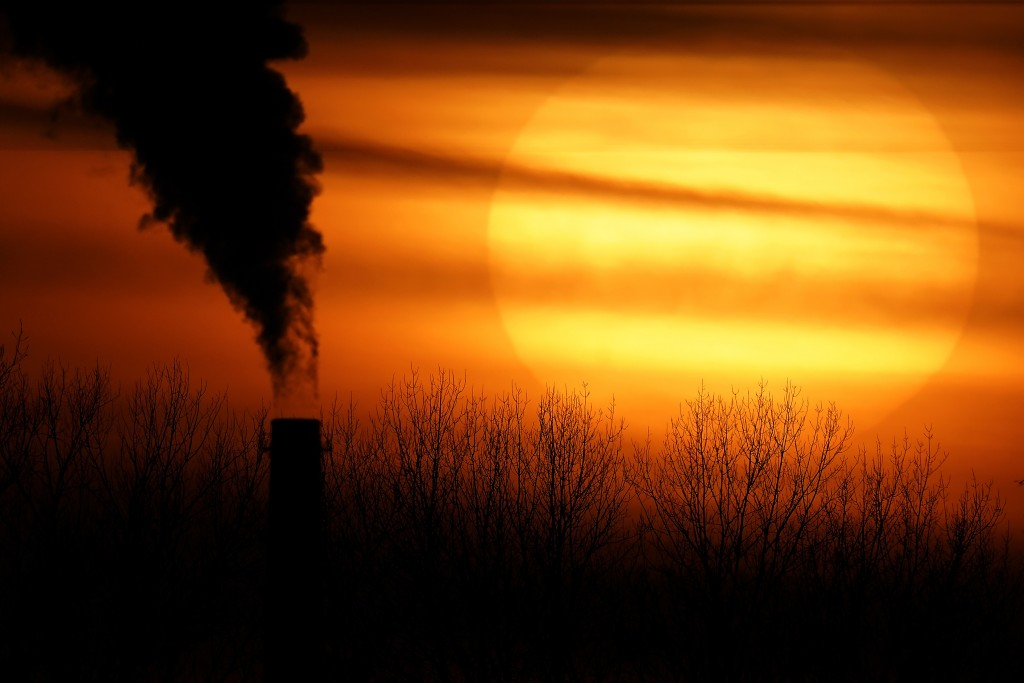 FILE - In this Feb. 1, 2021 file photo, emissions from a coal-fired power plant are silhouetted against the setting sun in Independence, Mo. President...