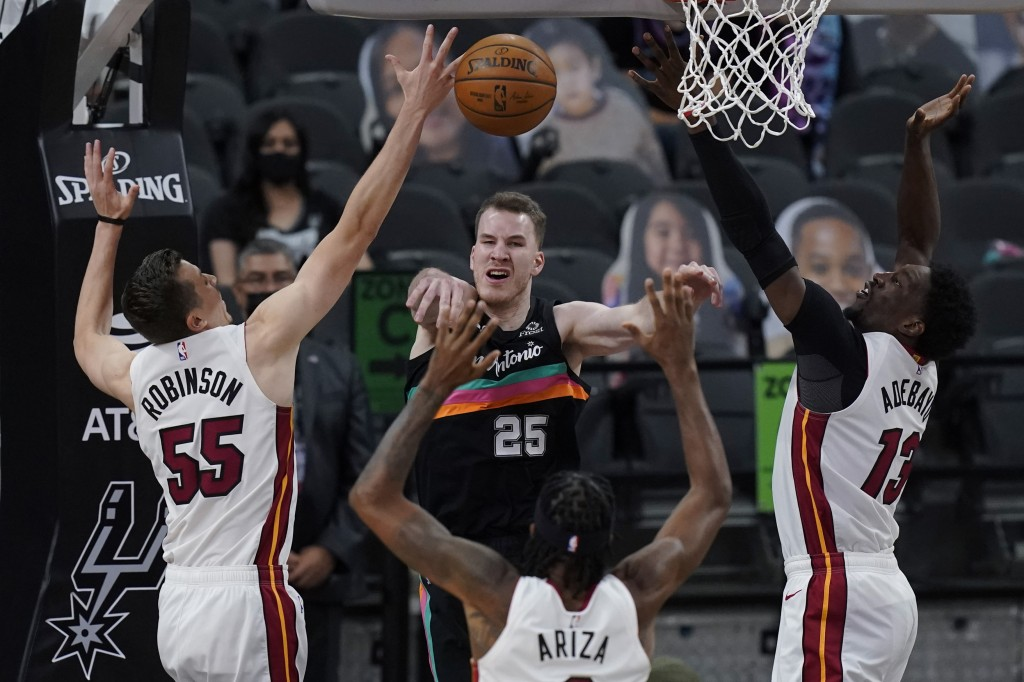 San Antonio Spurs center Jakob Poeltl (25) passes the ball as he is pressured by Miami Heat defenders Duncan Robinson (55), Trevor Ariza (8) and Bam A...