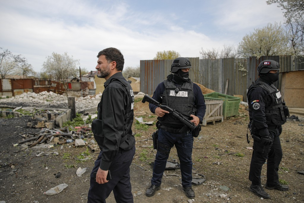 Octavian Berceanu, left, the head of the National Environmental Guard walks through scrape littered back yards during a raid in Vidra, Romania, Tuesda...