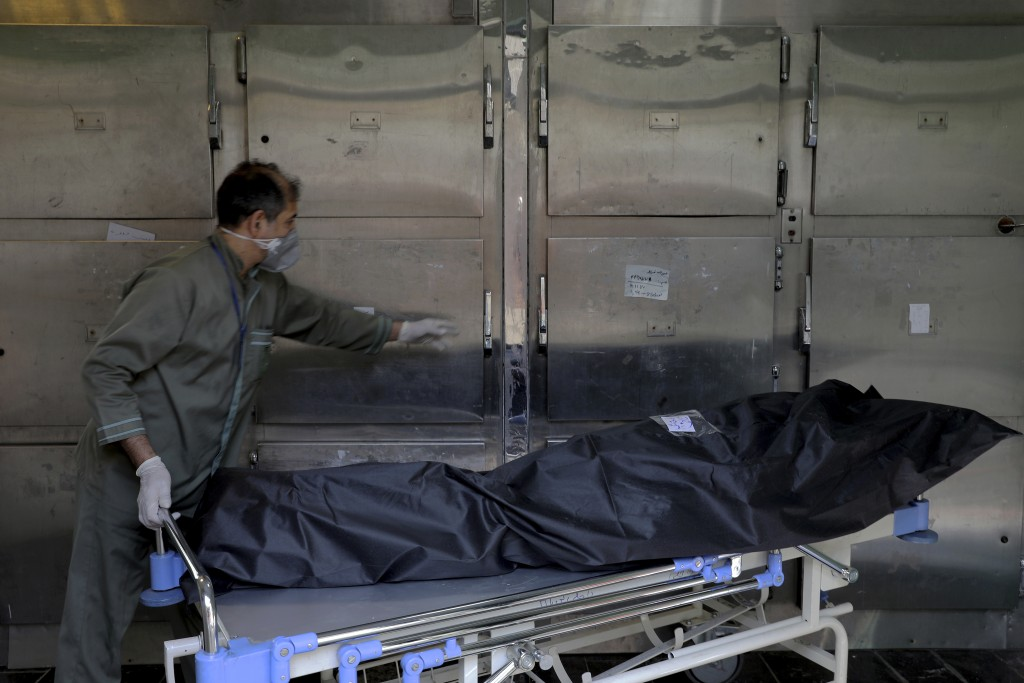 A hospital worker moves the body of a patient who died from COVID-19, at the morgue of the Shohadaye Tajrish Hospital in Tehran, Iran, Sunday, April 1...