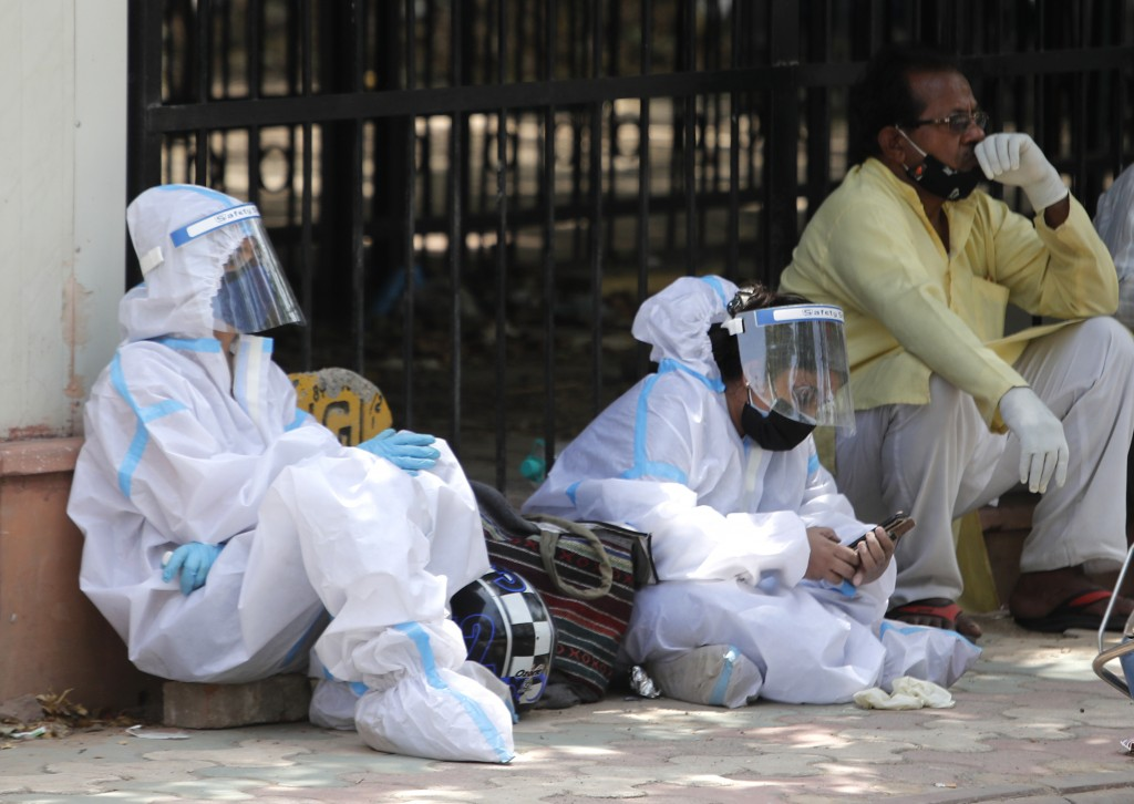 People in personal protective suits wait outside a mortuary to collect the body of their relative who died of coronavirus, in New Delhi, India, Monday...