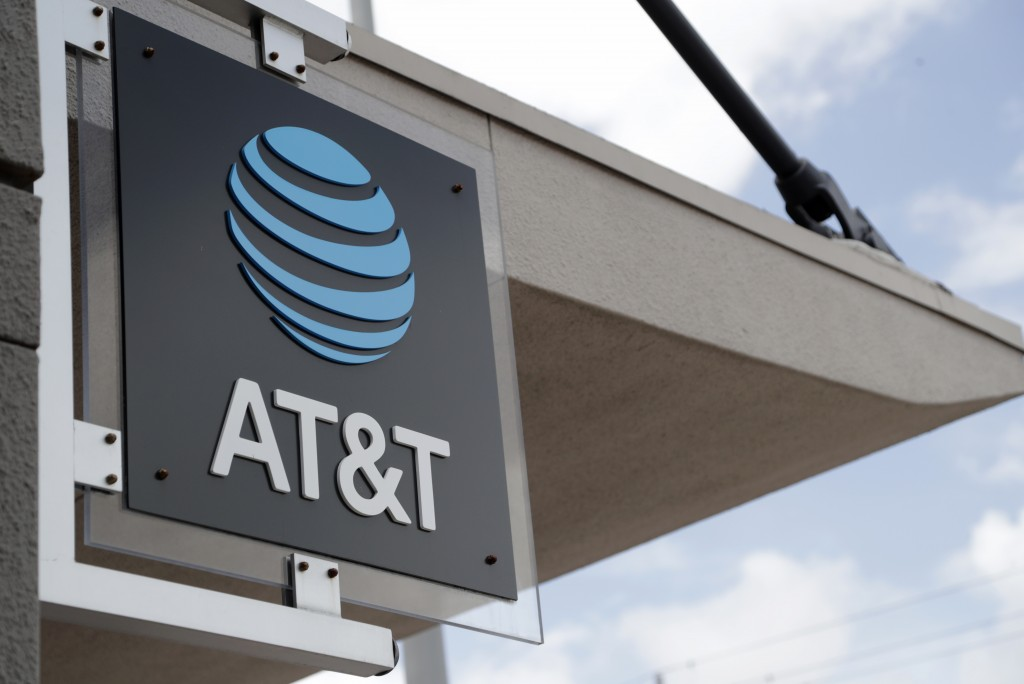 FILE - In this July 18, 2019 photo, a sign is displayed at an AT&T retail store in Miami.  Shares of AT&T Inc. rose Thursday, April 22, 2021 after the...
