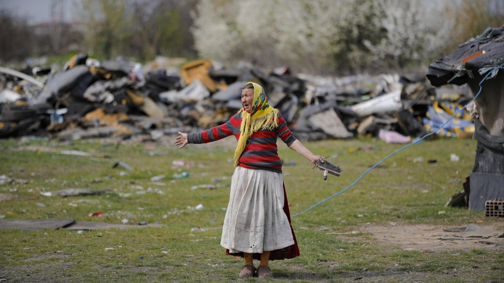 A woman gestures during a raid by the National Environmental Guard in Vidra, Romania, Tuesday, April 13, 2021. Many people in the Roma community in SI...