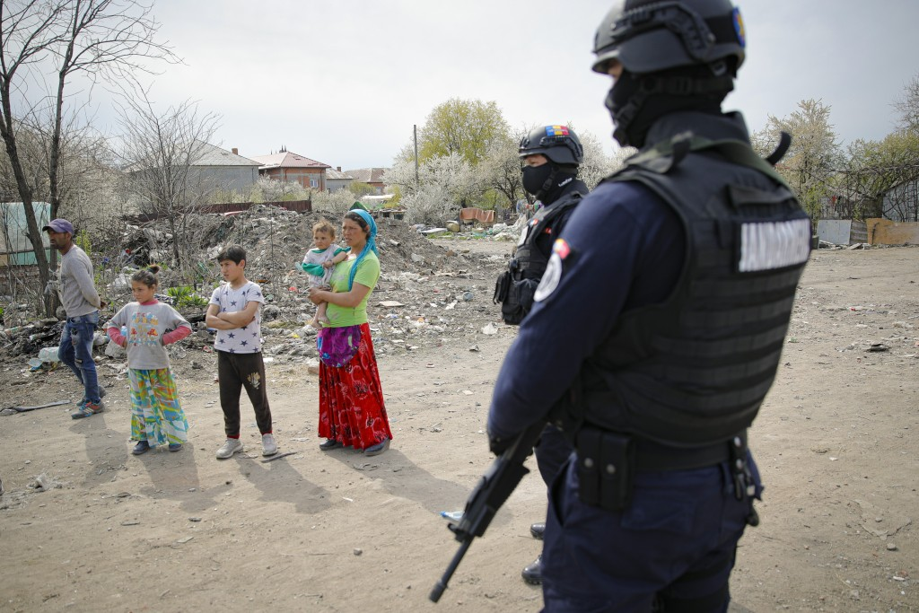 Riot police officers provide security during a raid of the National Environmental Guard through scrape littered back yards in Vidra, Romania, Tuesday,...