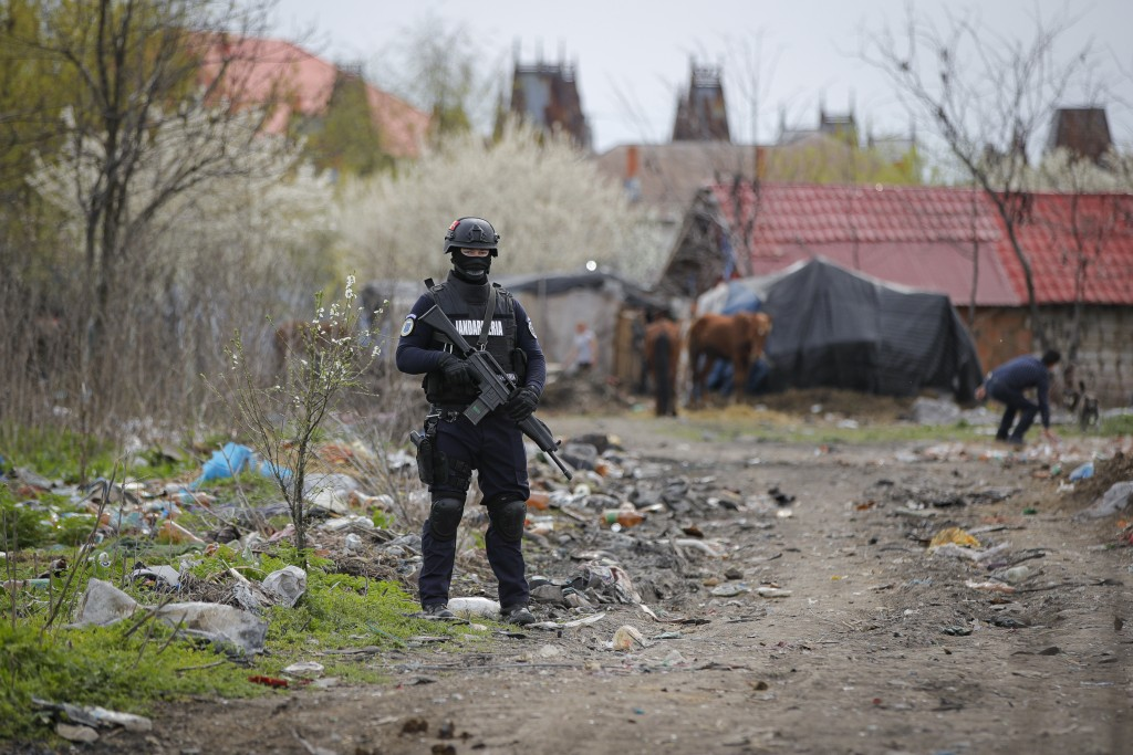 A riot police officer provides security during a raid of the National Environmental Guard through scrape littered back yards in Vidra, Romania, Tuesda...