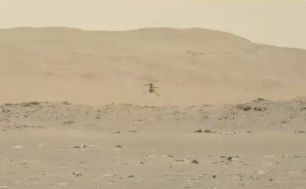 In this image from video made available by NASA, the Mars Ingenuity helicopter hovers above the surface of the planet during its second flight on Thur...