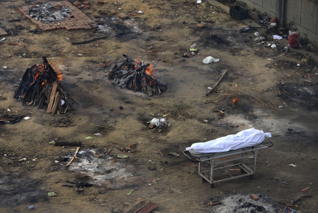 Multiple funeral pyres of those patients who died of COVID-19 disease are seen burning at a ground that has been converted into a crematorium for mass...