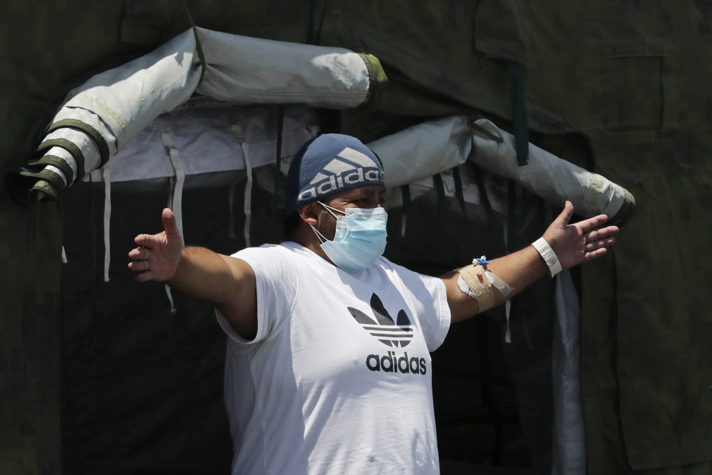 A COVID-19 patient does breathing exercises at the entrance of a tent set up to treat new coronavirus cases outside the Social Security Hospital, shor...