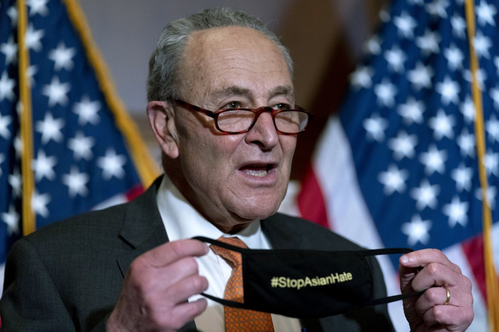 Senate Majority Leader Chuck Schumer of N.Y., holds up his mask that reads #StopAsianHate as he speaks at a news conference after the Senate passes a ...