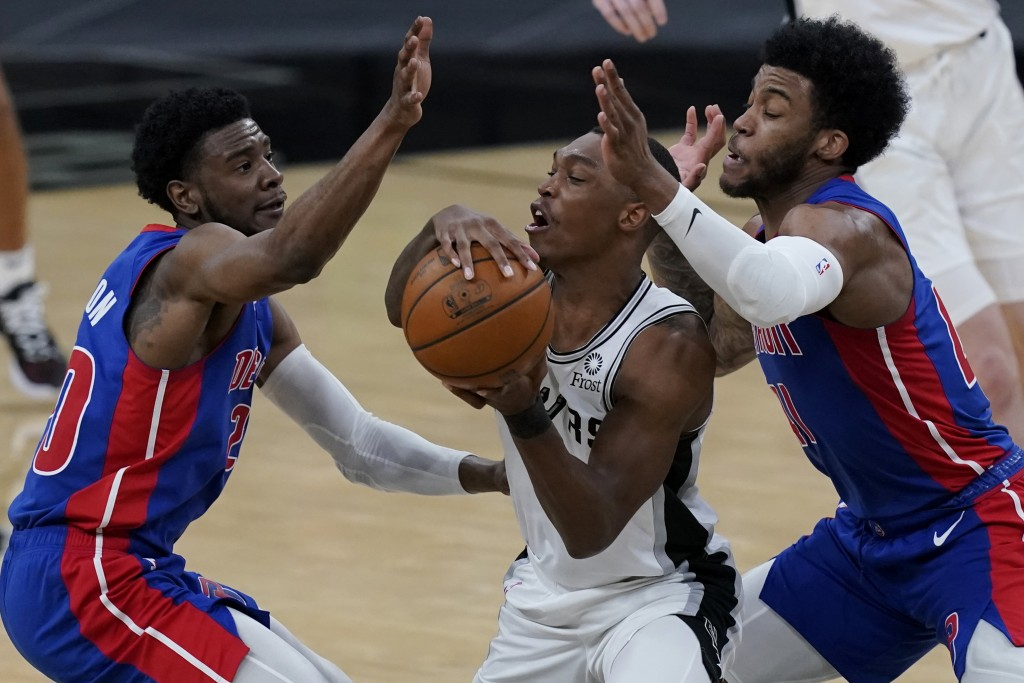 San Antonio Spurs guard Lonnie Walker IV, center, is pressured by Detroit Pistons guard Josh Jackson, left, and forward Saddiq Bey, right, during the ...