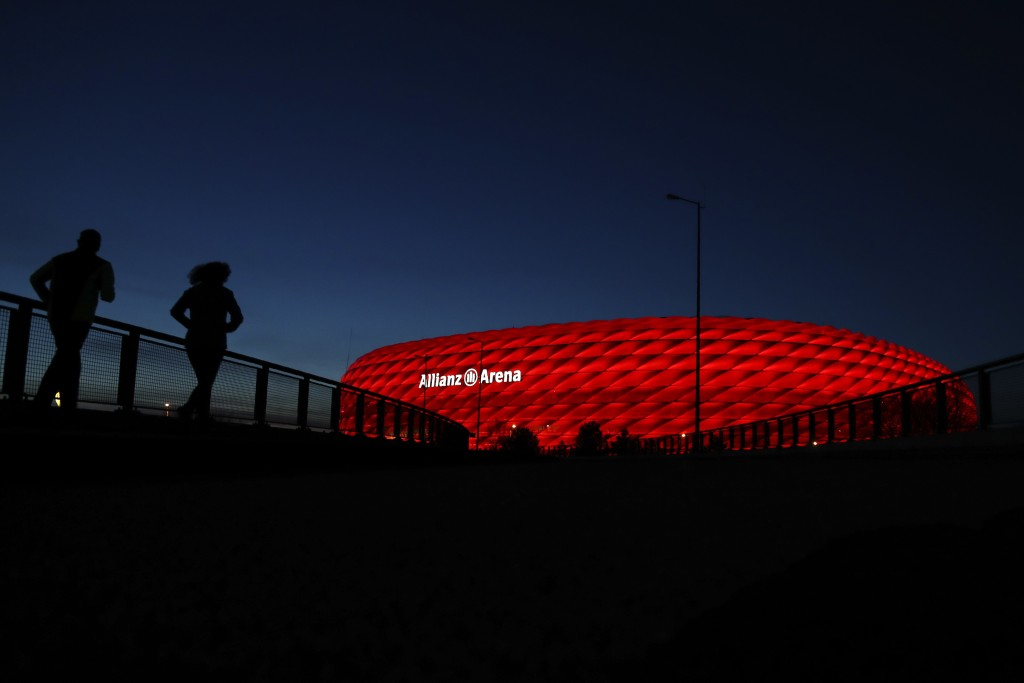 FILE-In this March 16, 2020 taken photo jogger make their way after the sun sets at the 'Allianz Arena' soccer stadium in Munich, Germany. European ru...