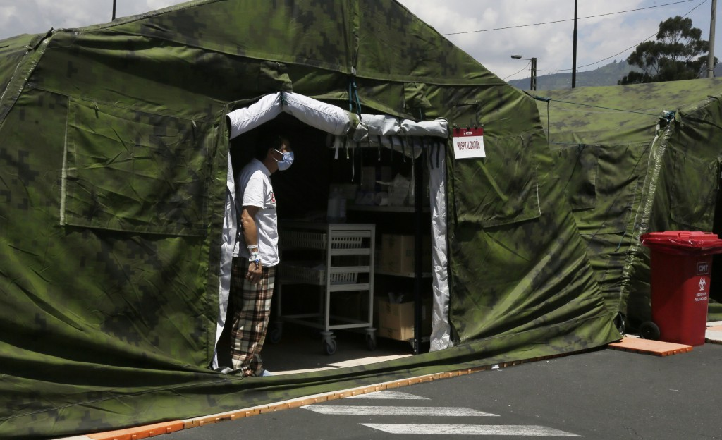 A COVID-19 patient looks for a relative to bring him personal items, from inside a tent set up outside the Social Security Hospital where patients are...