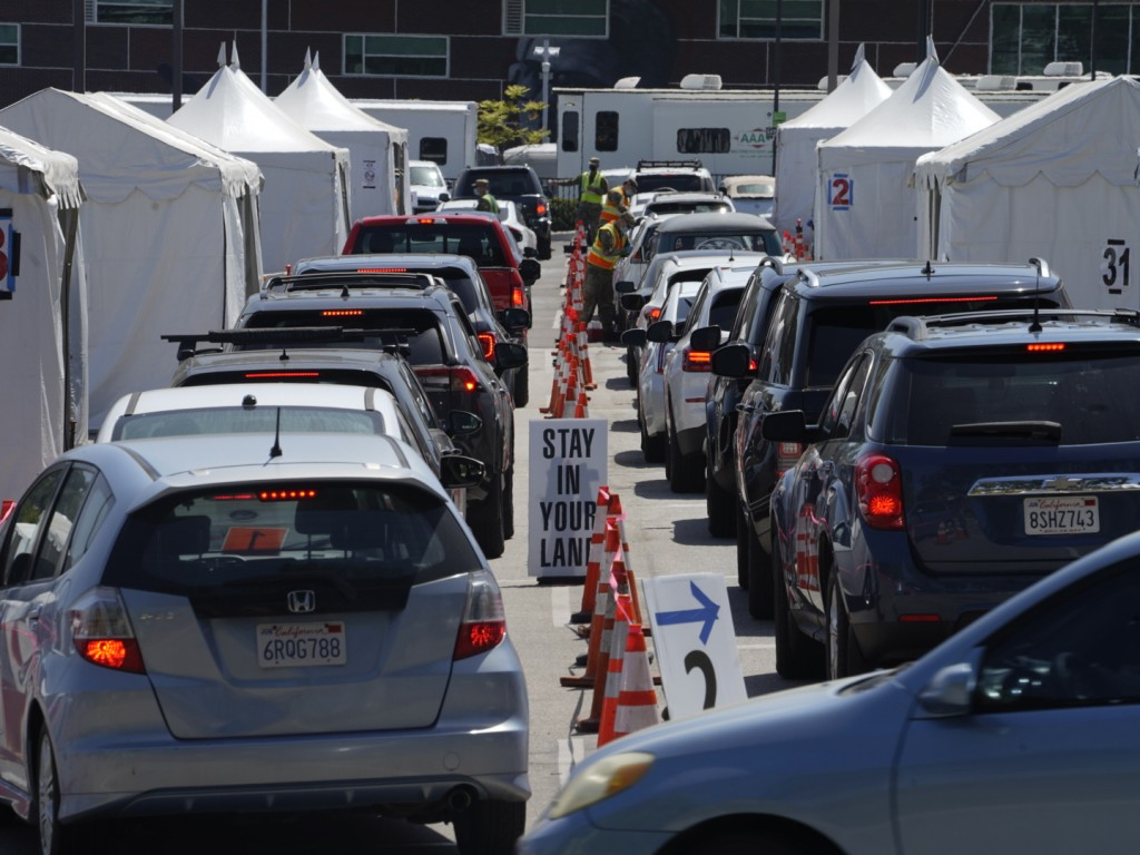 FILE - In this April 8, 2021, file photo motorists sit inside their vehicles as they wait their turn to be inoculated with a COVID-19 vaccine at the C...