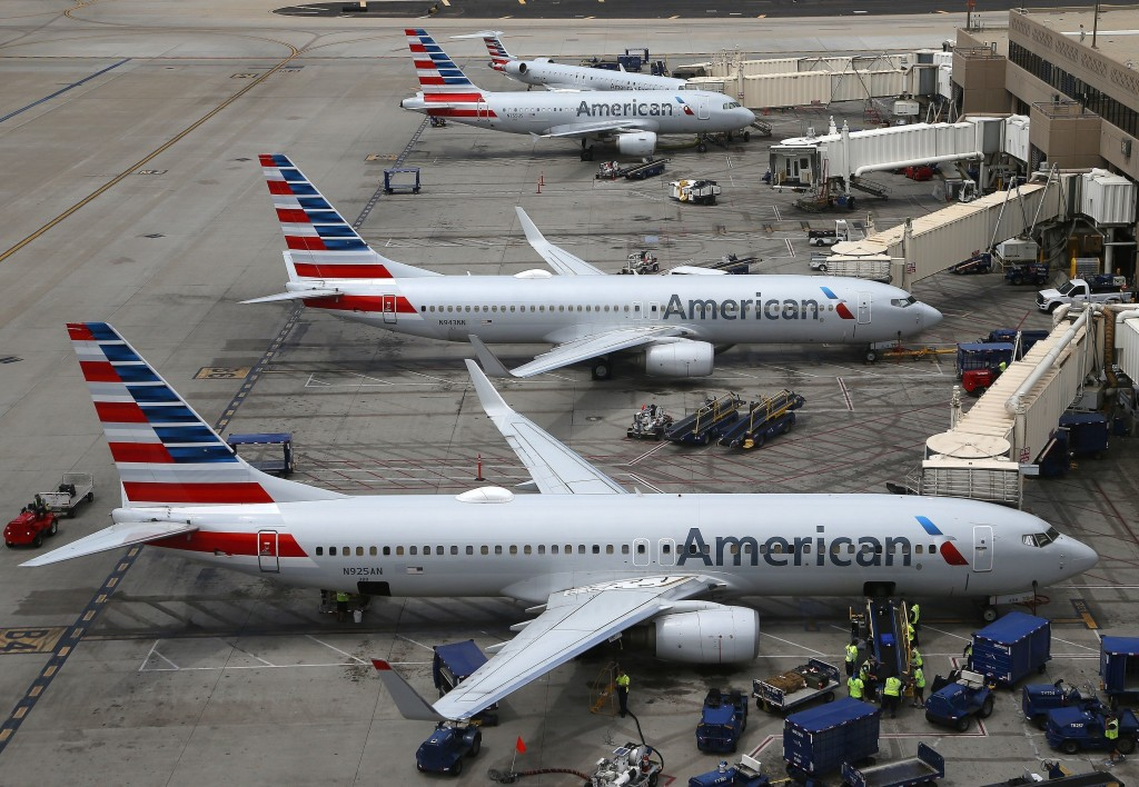 FILE - In this July 17, 2019 file photo American Airlines planes are parked on the tarmac at Phoenix Sky Harbor International Airport in Phoenix. Amer...