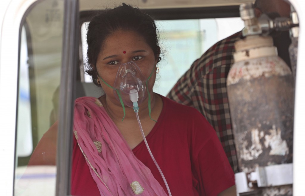 A COVID-19 patient wearing oxygen mask waits inside a vehicle to be attended and admitted in a dedicated COVID-19 government hospital in Ahmedabad, In...