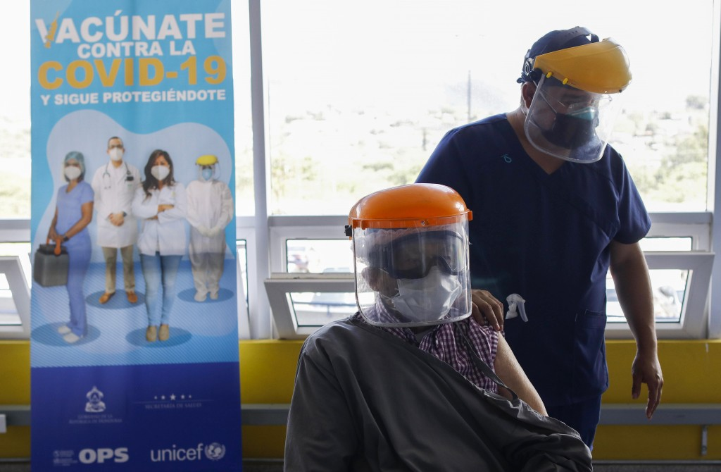 Roberto Maradiaga, 70, a retired doctor, is helped by his son Luis Roberto, while he waits for the Russian COVID-19 vaccine Sputnik V, as part of a va...