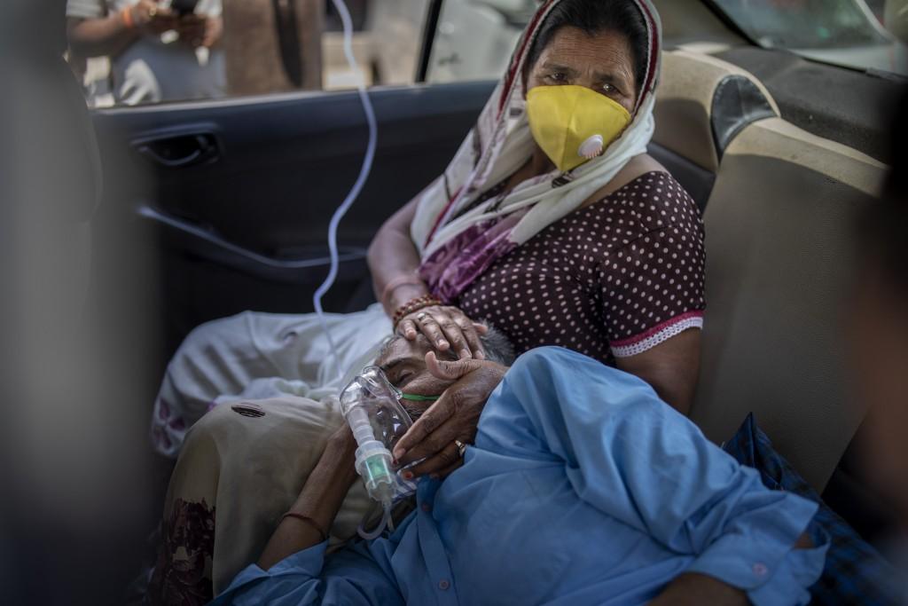 印度新德里民眾因等不到醫院病床,由家屬陪伴在院外車上使用呼吸器等待入院。(美聯社圖片)