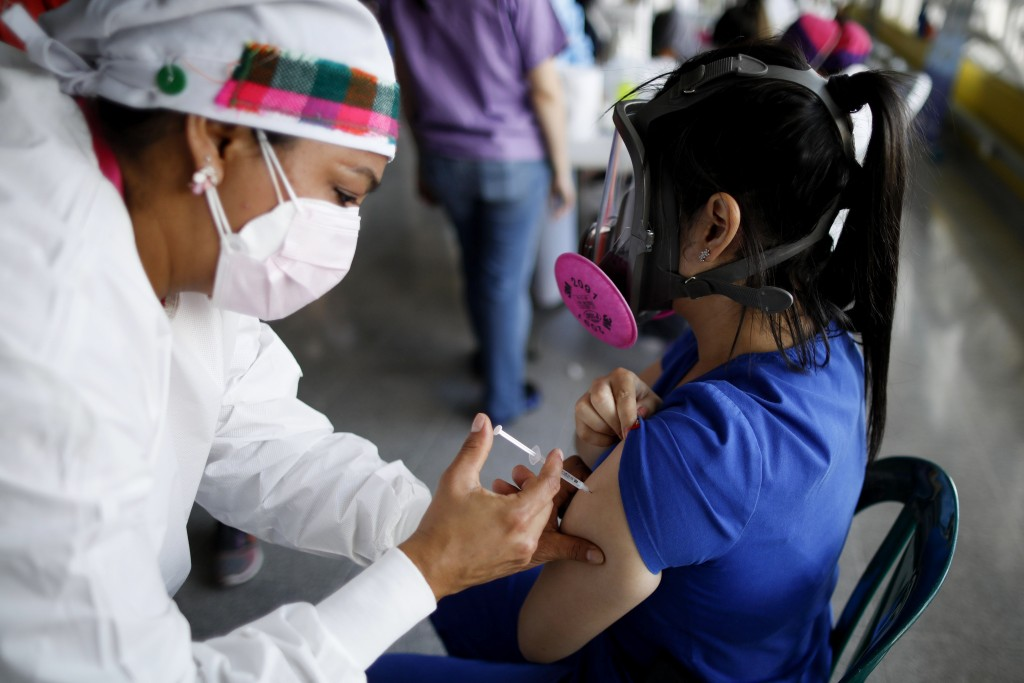 FILE - In this April 23, 2021, file photo, a health care worker inoculates Dr. Virma Rivas with the Sputnik V COVID-19 vaccine, as part of a vaccinati...