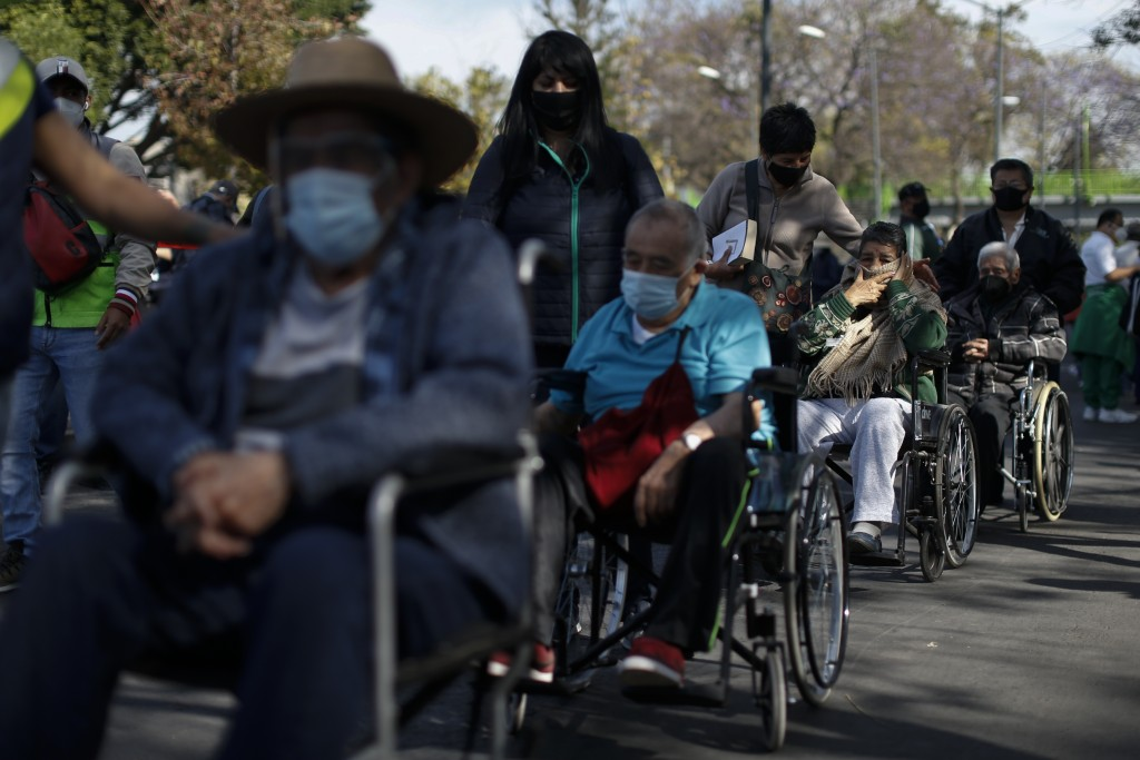 FILE - In this Feb. 24, 2021, file photo, elderly residents of the Iztacalco borough wait in line to receive doses of the Russian COVID-19 vaccine Spu...