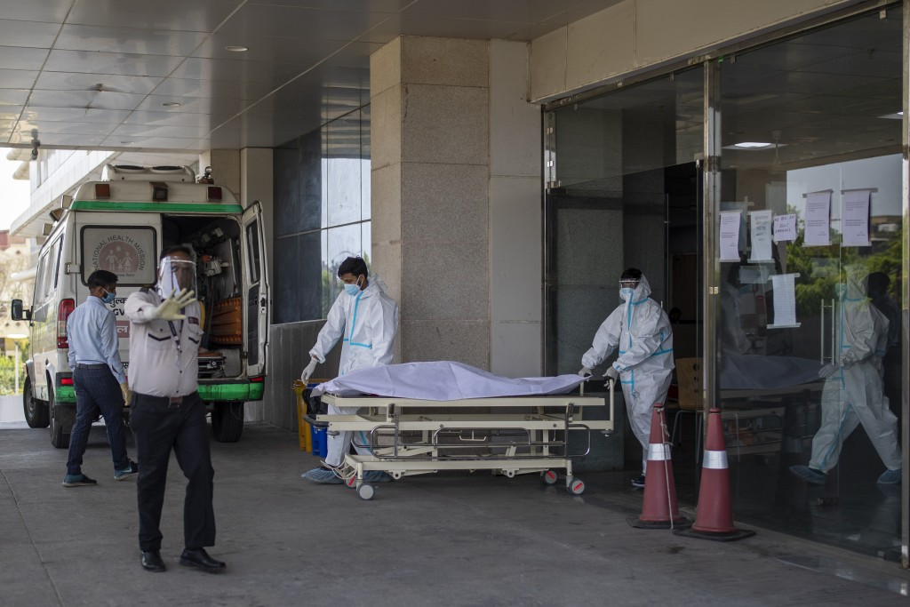 FILE - In this April 21, 2021, file photo, security guard objects to taking taking pictures as hospital staff shift the body of a COVID-19 patient on ...