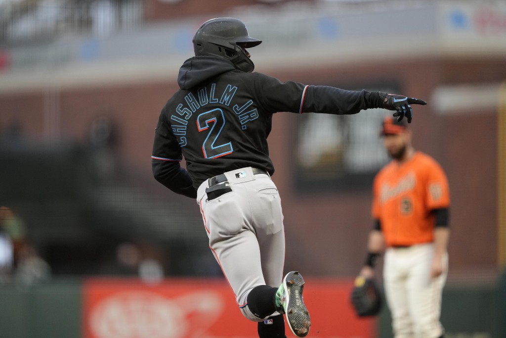 Miami Marlins' Jazz Chisholm Jr. (2) points to the teammates in the dugout as he rounds the bases after hitting a solo home run against the San Franci...