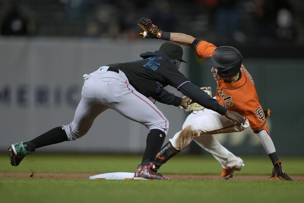 San Francisco Giants' Mauricio Dubon (1) slides into second base for a double past the tag of Miami Marlins second baseman Jazz Chisholm Jr. during th...