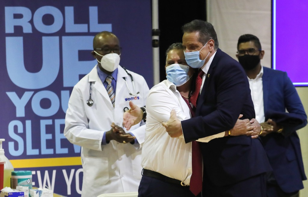 Gov. Andrew Cuomo embraces Radhames Rodriguez, President of United Bodegas of America, after Rodriguez received a Pfizer COVID-19 vaccination shot at ...