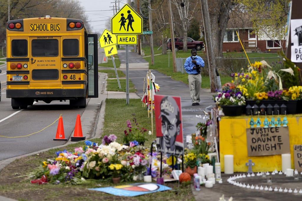 A school bus driver stops to look at a makeshift memorial at the site where Daunte Wright was killed a day after he was laid to rest, Friday, April 23...