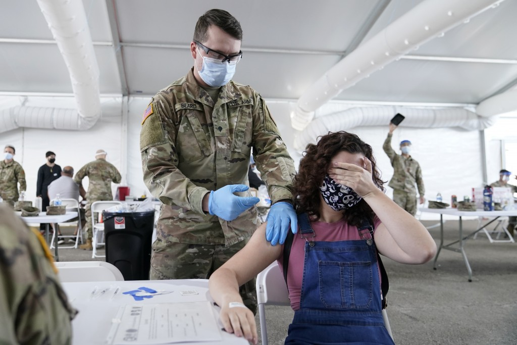 FILE - In this April 5, 2021, file photo, Leanne Montenegro, 21, covers her eyes as she doesn't like the sight of needles, while she receives the Pfiz...