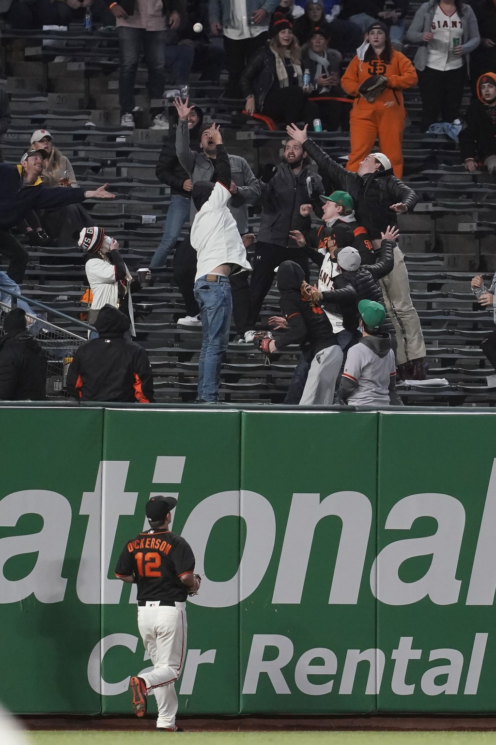 San Francisco Giants left fielder Alex Dickerson (12) looks up as fans reach for a solo home run hit by Miami Marlins' Jon Berti during the seventh in...