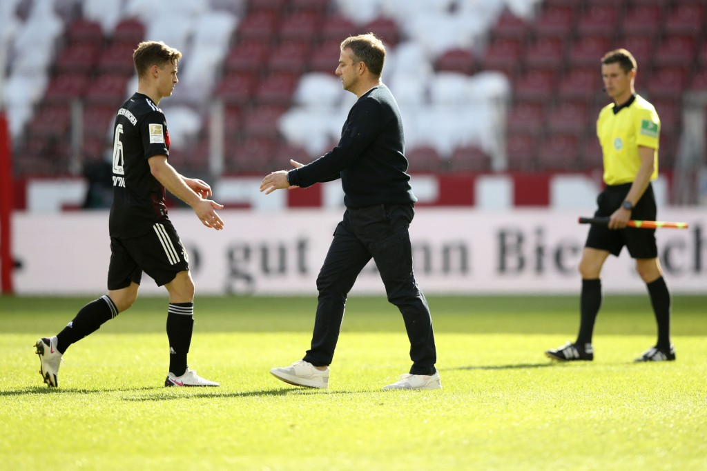 Bayern's head coach Hans-Dieter Flick, right, and Bayern's Joshua Kimmich shake hands after the German Bundesliga soccer match between FSV Mainz and F...
