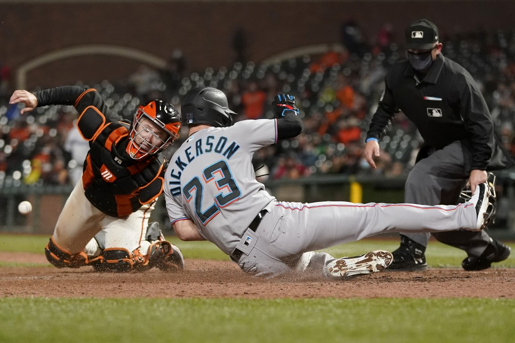 Miami Marlins' Corey Dickerson (23) scores past San Francisco Giants catcher Buster Posey, left, during the ninth inning of a baseball game in San Fra...