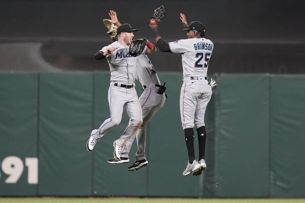 Miami Marlins' Corey Dickerson, from left, celebrates with Magneuris Sierra and Lewis Brinson after they defeated the San Francisco Giants in a baseba...