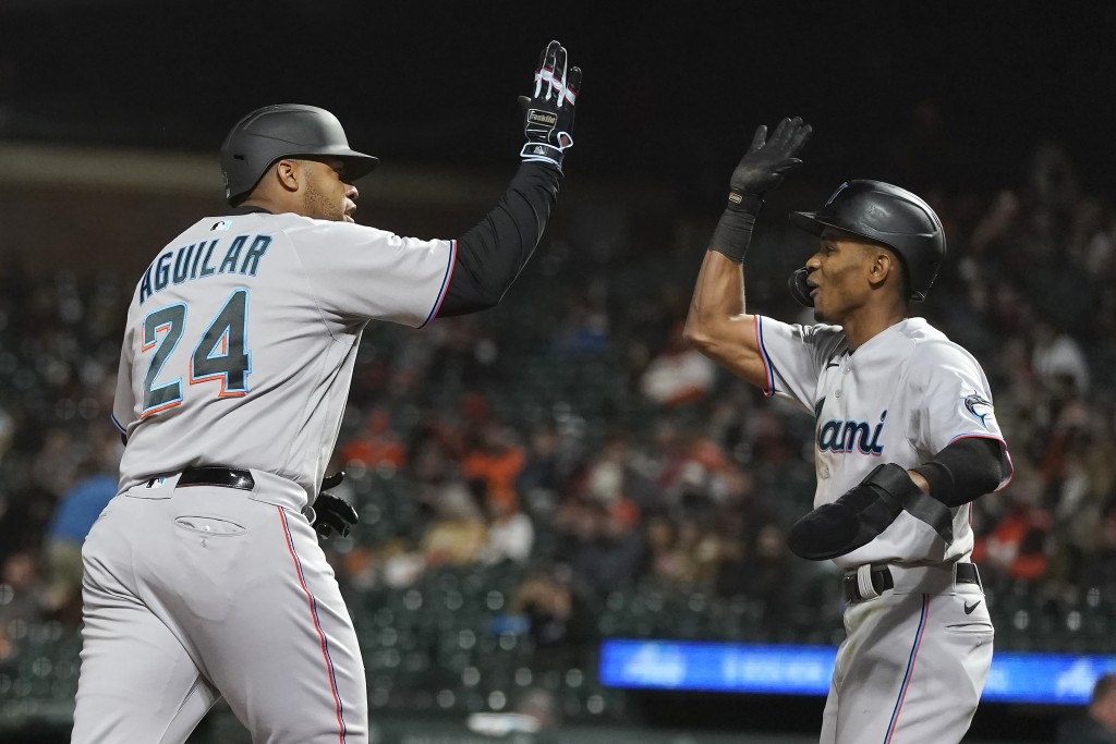 Miami Marlins' Jesus Aguilar (24) celebrates after hitting a two-run home run that also scored Magneuris Sierra, right, during the ninth inning of a b...
