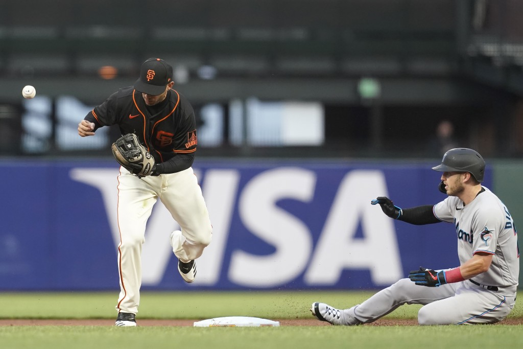 Miami Marlins' Corey Dickerson, right, is safe at second base as San Francisco Giants second baseman Tommy La Stella, left, makes an error during the ...