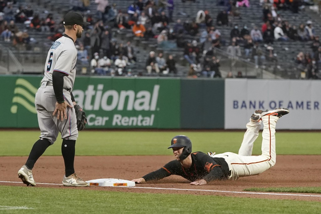 San Francisco Giants' Buster Posey, right, slides safely into third base next to Miami Marlins third baseman Jon Berti during the fifth inning of a ba...